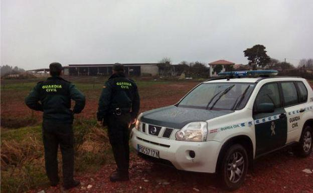 Dos agentes de la Guardia Civil, junto a una explotación agraria. /Guardia Civil