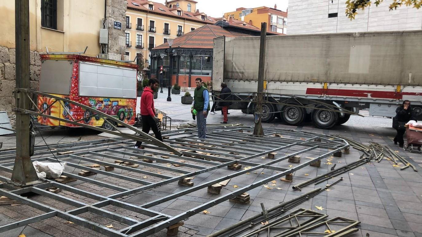 Dos feriantes desmontan una atracción en la plaza de la Rinconada. /El Norte