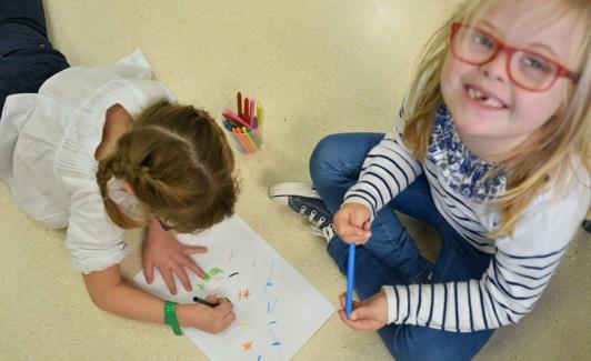 Una niña con trisomía 21 dibuja junto a una compañera sin discapacidad. /DOWN ESPAÑA